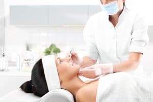 Doctor performs a microneedling procedure for restoring collagen in the face